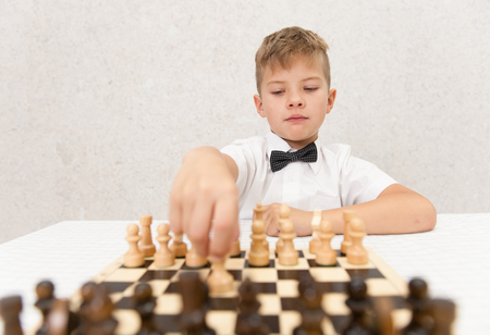 Boy playing a game of chess. Space for text.