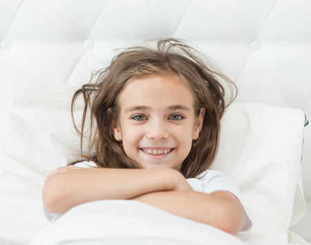 smiling girl lies on the bed in the morning.