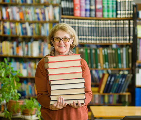 Happy senior woman with books in library. Stock Photo