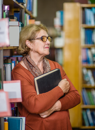 Senior woman chooses a book in the library.