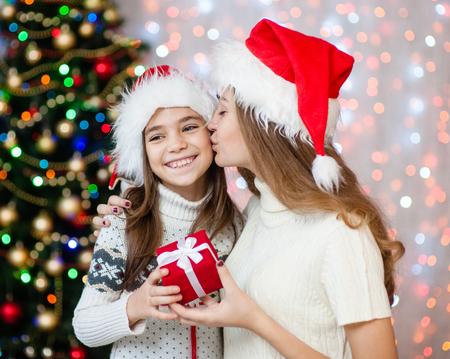 Mamá besa a su hija y le da un regalo de Navidad. Foto de archivo