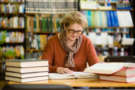 haute femme lisant un livre dans la bibliothèque.