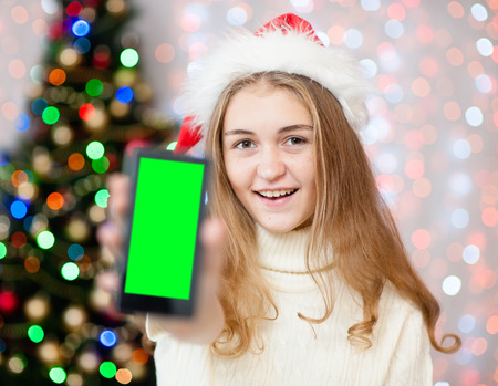 Happy young woman  in red christmas hat  holding smartphone with green screen.