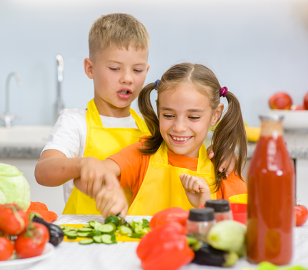 niños desayunando: older brother teaches her sister to cut vegetables for lunch. Foto de archivo