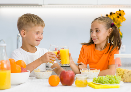 Girl and boy clink glasses with orange juice at breakfast.