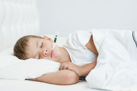Sick boy with thermometer in mouth sleeping on the bed. Stock Photo