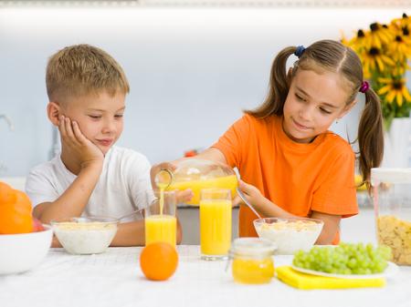 Little girl pours orange juice to her brother. Banco de Imagens