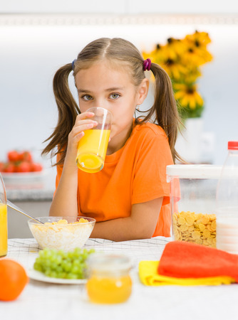girl drinks orange juice for breakfast.