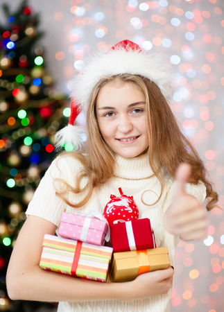 Happy young woman holding many present boxes and showing thumbs up. Stock Photo