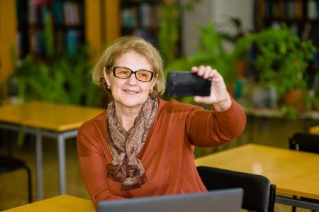 Happy senior woman taking selfie in library. Stock Photo