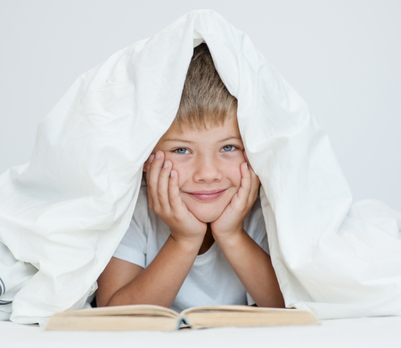 bedtime story: boy is reading a book under the blanket.