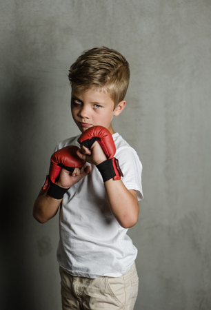 Beaten young boy with red boxing gloves.