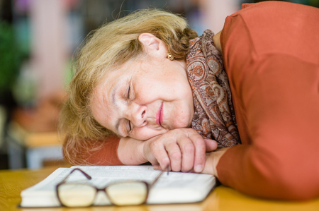 Tired elderly woman is sleeping in a library.