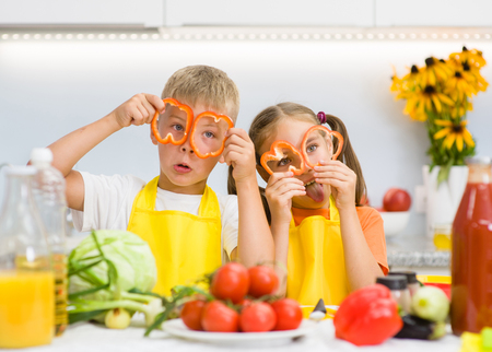 niños desayunando: Funny children having fun with food vegetables at kitchen holds pepper before his eyes like in glasses Foto de archivo
