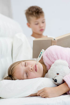 Little boy reads the book to the sick sister. Stock Photo