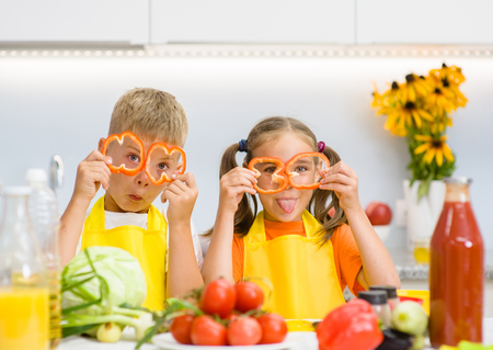 niños desayunando: Funny children having fun with food vegetables at kitchen holds pepper before his eyes like in glasses. Foto de archivo