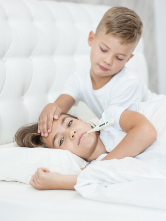 boy touches his sisters forehead, checking the temperature.