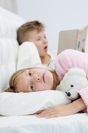 brother reads the book to the sick sister. Stock Photo