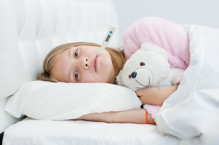sick girl lying on the bed with a thermometer in mouth. Stock Photo