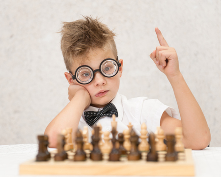 smart boy sits at the chessboard and shows finger up. Idea concept. Stock Photo
