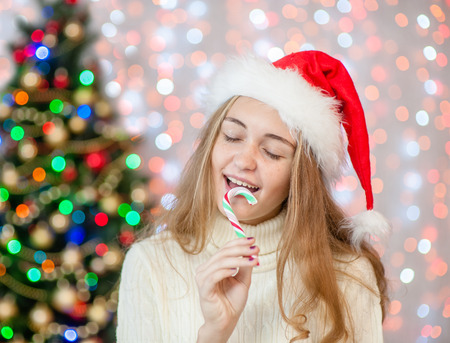 teen girl in red santa christmas hat with candy cane. Space for text.
