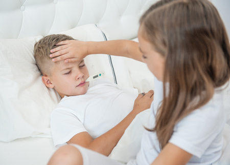 Girl touches forehead to her sick brother, checking the temperature.