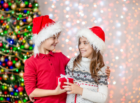 Happy boy gives the girl a gift for Christmas. Stock Photo