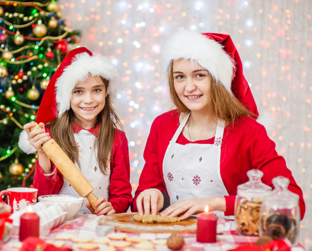 Happy mom and daughter cooking Christmas cookies.