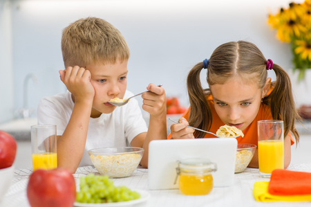 Kids eat breakfast while watching a movie on a tablet pc Stock Photo