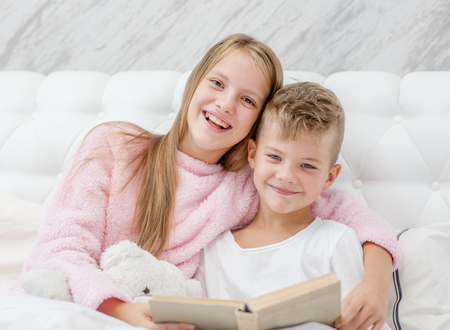 the elder sister reads a funny book to her younger brother. Stockfoto