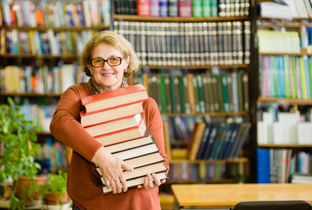 Senior mujer con ordenador portátil en la biblioteca.