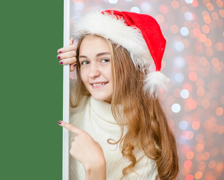 Happy girl in red christmas hat above  green banner and pointing on empty space. Space for text.