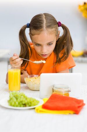 Little girl is having breakfast while watching the movie on the tablet.