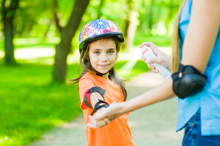 Mother spraying insect repellents on skin girl. Stock Photo