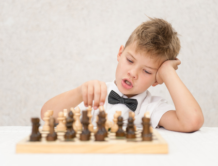 boy pondered before making a move, playing chess.