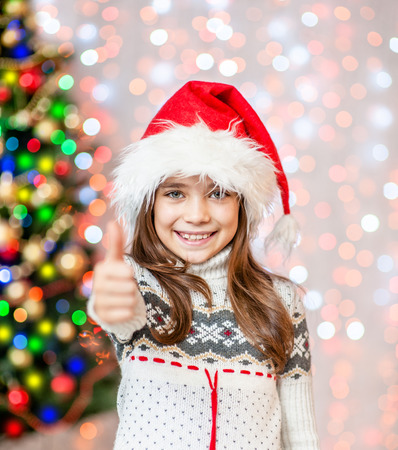 happy little girl in red santa christmas hat showing thumbs up.