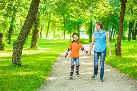 Mother and daughter have fun in nature, rollerblading. Space for text. Banco de Imagens