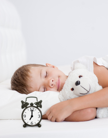 Happy little girl sleeping in bed with toy bear. Space for text. Zdjęcie Seryjne - 92720070