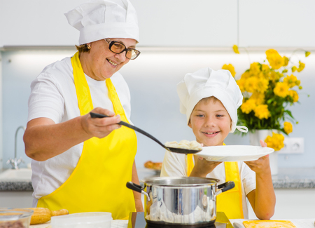 Senior woman  with a happy grandson is cooked in the kitchen of dumplings.