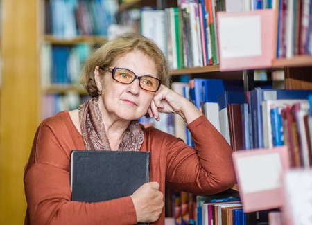 thoughtful elderly woman standing with book in library. Stock Photo