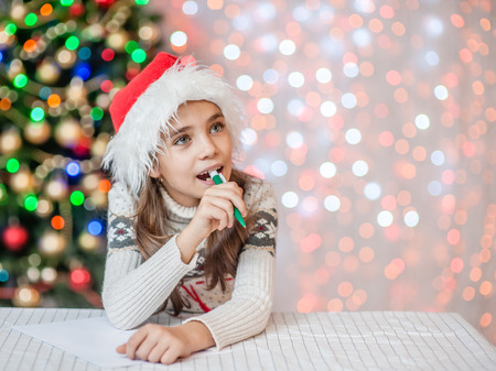girl in red christmas hat thinking what to write in a letter to Santa Claus. Looking away. Space for text. Foto de archivo