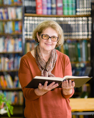 senior woman with open book in library.