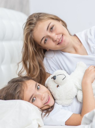Young mother with her daughter on the bed.