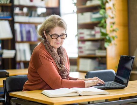 Senior woman using laptop in library. Foto de archivo