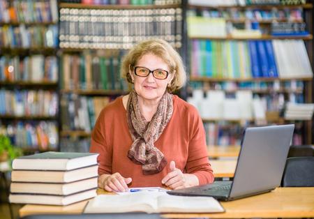 bonne femme âgée utilisant un ordinateur portable dans la librairie