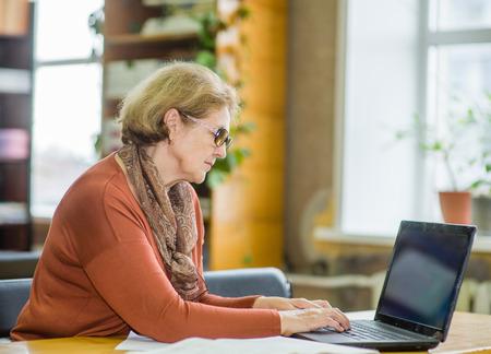 図書館でラップトップで働く年配の女性。 写真素材