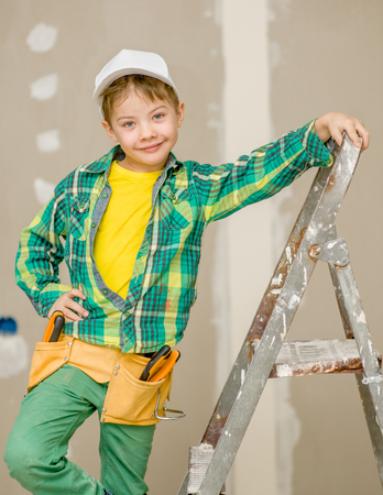 Smiling boy on a ladder with tool belt.