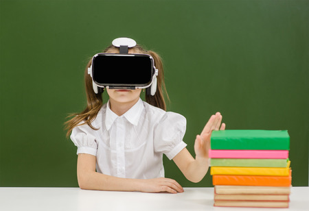 little girl with virtual reality headset refuses the books on the background of a school board.