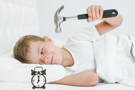 Lazy boy splits alarm clock with hammer. Stock Photo