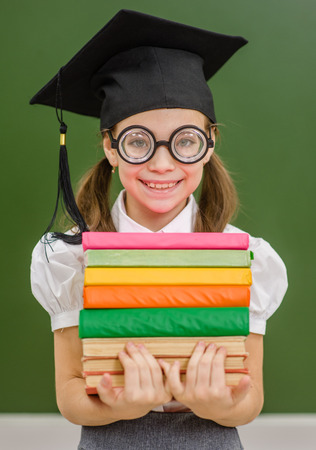 Happy little nerd student girl  with in graduation hat and books on the background of a school board.